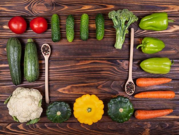 Vários vegetais coloridos em uma colina de comida de fundo de madeira