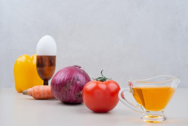 Vários vegetais com ovo e óleo na superfície branca