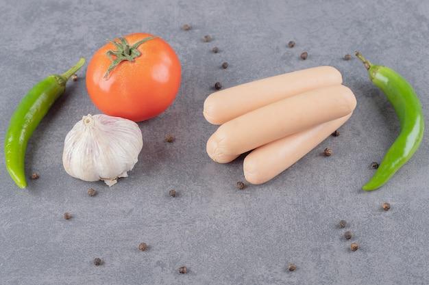Vários vegetais com salsichas na superfície de mármore