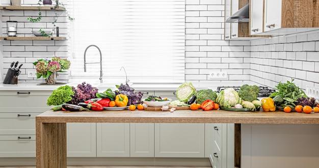 Vários vegetais em uma mesa de madeira contra a parede do interior de uma cozinha moderna.