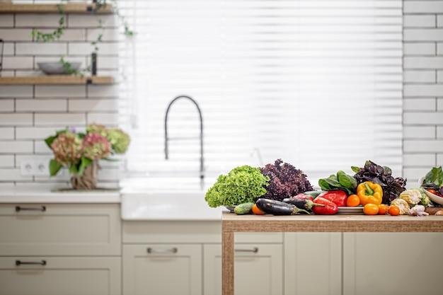 Vários vegetais em uma mesa de madeira contra o espaço do interior de uma cozinha moderna.