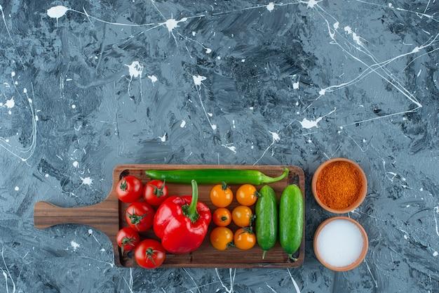 Vários vegetais em uma placa ao lado de sal e especiarias, no fundo de mármore.