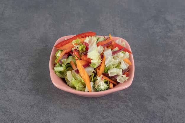 Vários vegetais fatiados em uma tigela rosa. foto de alta qualidade
