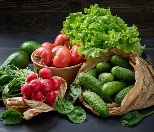 Vários vegetais frescos em sacos de papel na mesa da cozinha de madeira
