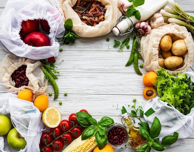 Vários vegetais orgânicos da fazenda, grãos, massas e frutas em sacolas de supermercado de embalagens reutilizáveis