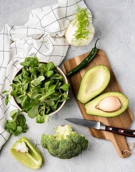 Vários vegetais verdes e panos de cozinha