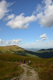 Vários viajantes caminhando ao longo do cume até o topo da montanha contra o céu azul
