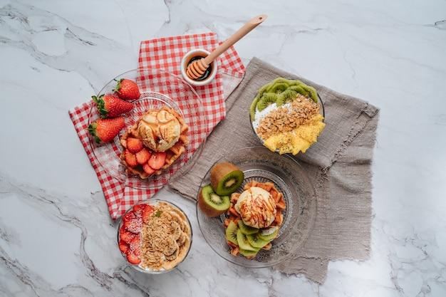Vários waffles servidos com frutas como morango e kiwi. mais uma bola de sorvete de baunilha