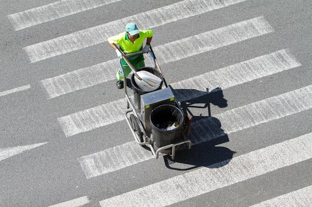 Varredor de rua empurrando um carrinho na faixa de pedestres. conceito de limpeza pública
