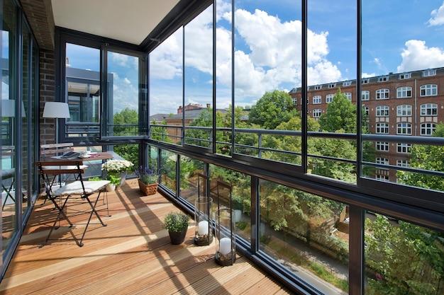 Varsóvia, polônia - 7 de agosto de 2018: varanda em um apartamento moderno com móveis, flores e vista para a cidade