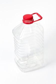 Vasilha grande de plástico transparente para água e outros líquidos com tampa vermelha sobre um fundo cinza claro com espaço de cópia.