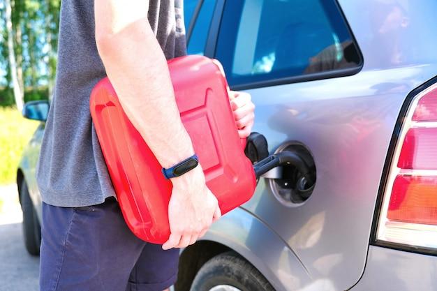 Vasilha vermelha nas mãos de um homem. encher um carro parado com gasolina de uma lata.