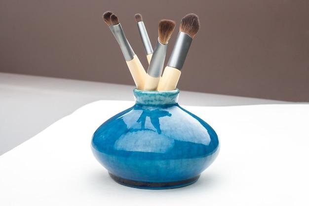 Vasinho azul com pincéis de maquiagem