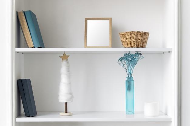 Vaso azul, moldura e livros nas prateleiras brancas. acessórios para casa azuis clássicos e livros nas prateleiras de parede