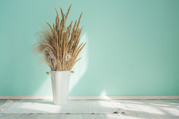 Vaso-balde de ferro branco com espigas secas de capim-dos-pampas contra o fundo de uma parede azul
