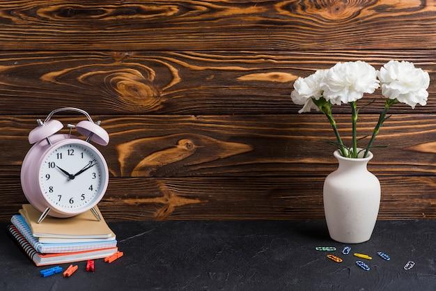 Vaso; clipe de papel colorido; prendedor e despertador em notebooks empilhados sobre o pano de fundo preto