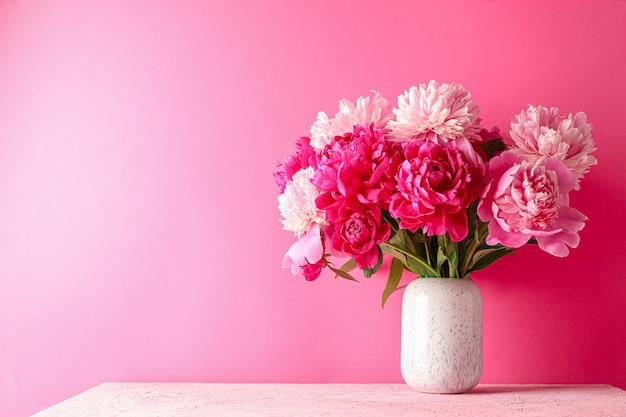 Vaso com buquê de peônias lindas na mesa-de-rosa contra a cor de fundo