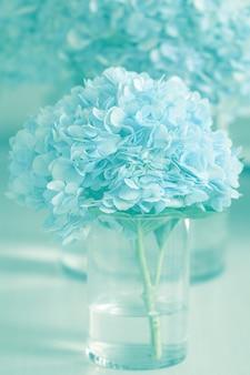 Vaso com flores de hortênsia azul bonita sobre uma mesa de madeira.
