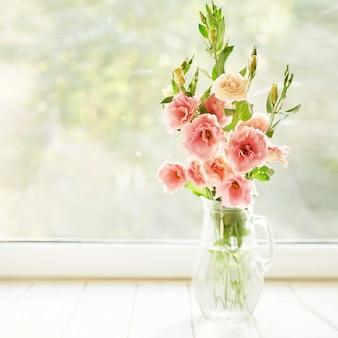 Vaso com flores eustoma sobre uma mesa contra uma janela