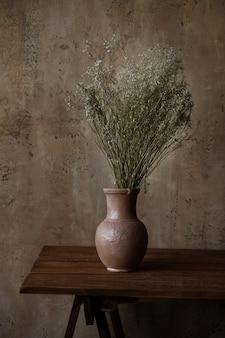 Vaso com flores secas em uma mesa marrom.