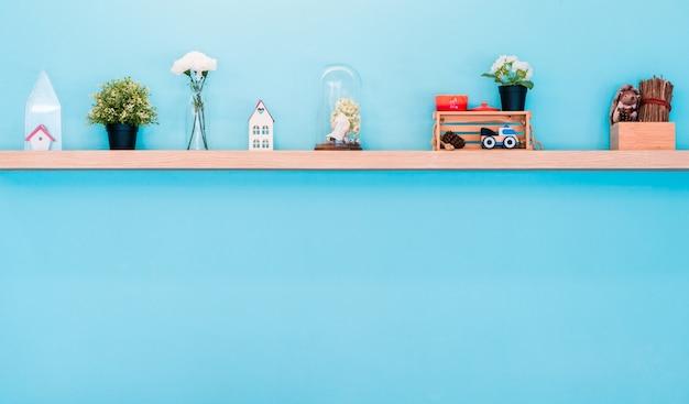 Vaso de brinquedo e flor de casa na decoração home prateleira de madeira, parede azul criativa com c limpo