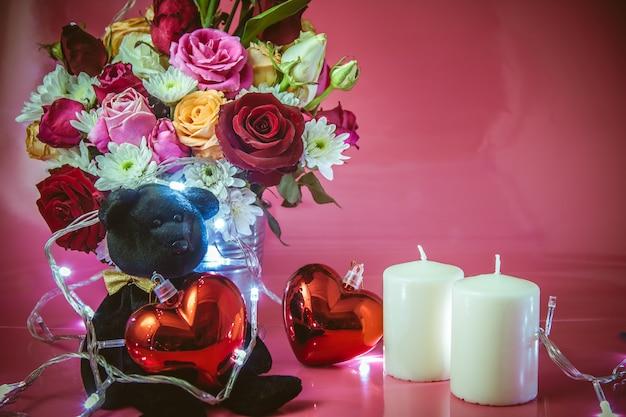 Vaso de buquê rosas, coração vermelho e vela branca