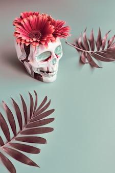 Vaso de caveira com flores de gérbera de cor coral e folhas de palmeira
