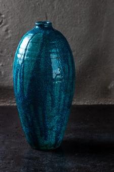 Vaso de cerâmico antigo de cor turquesa sobre fundo cinza cimento, antigo vaso grande e alto projetado para flores, decoração requintada