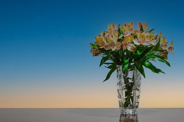 Vaso de cristal com flores e espaço para texto.