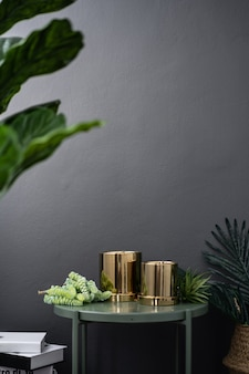 Vaso de espelho ouro isolado na mesa lateral de metal verde em plantas artificiais e na parede pintada de cinza