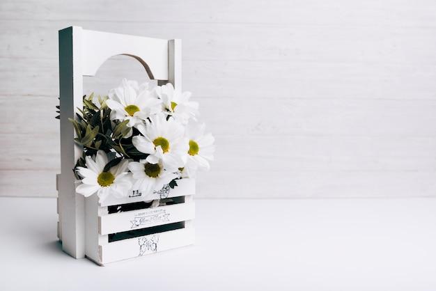 Vaso de flor branca de madeira contra o pano de fundo de madeira