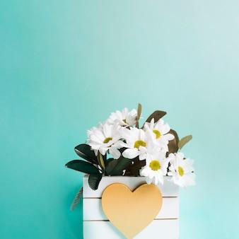 Vaso de flor de forma de coração no fundo turquesa