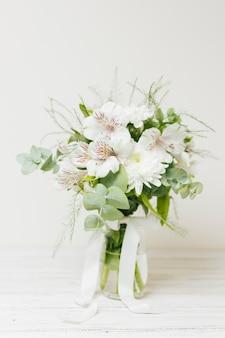 Vaso de flor de jasminum auriculatum com fita branca na mesa de madeira