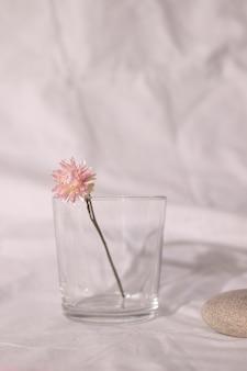 Vaso de flor rosa seca na mesa com tecido branco