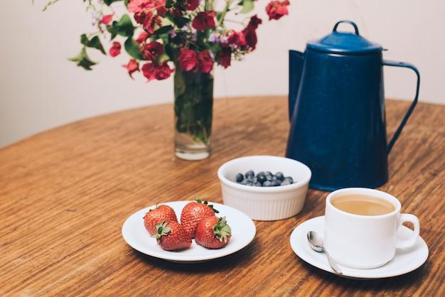 Vaso de flores; bagas e xícara de café na mesa