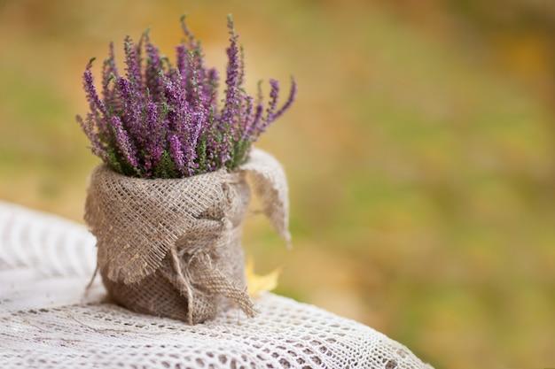 Vaso de flores com um véu sobre uma mesa de estilo rústico