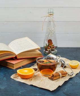 Vaso de flores e uma xícara de chá com jornal, canela, laranja e um coador de chá