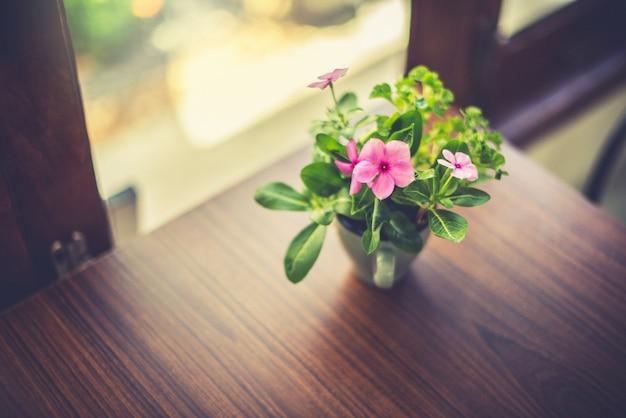 Vaso de flores em cima da mesa na janela