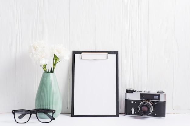 Vaso de flores; óculos; câmera e papel em branco na área de transferência contra a parede de madeira em branco