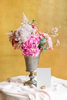 Vaso de flores perto de um cartão sobre uma mesa