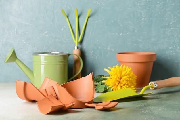 Vaso de flores quebrado e ferramentas de jardinagem na mesa