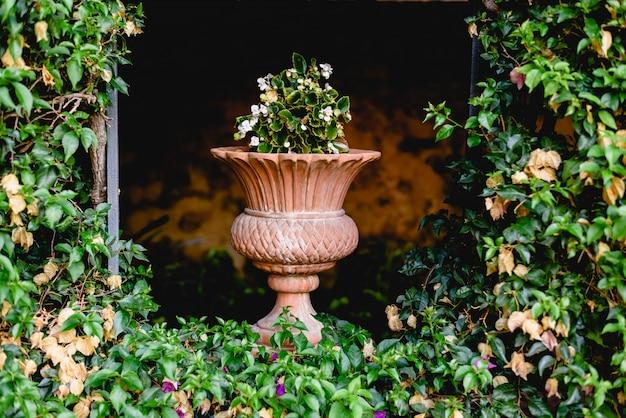 Vaso de pedra cinzelado antigo em um jardim europeu com flores.