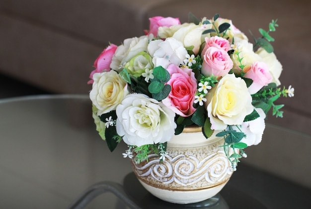 Vaso de rosa de plástico colorido colocado sobre a mesa na sala de estar