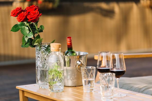 Vaso de rosas vermelhas; balde de gelo e taças de vinho na mesa de madeira