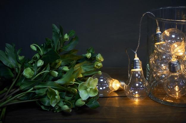Vaso de vidro cheio de lâmpadas luminosas e um buquê de heléboro