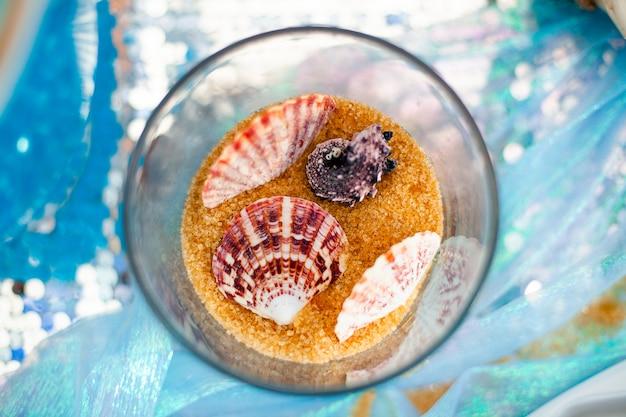 Vaso de vidro com areia de açúcar mascavo doce e conchas diferentes