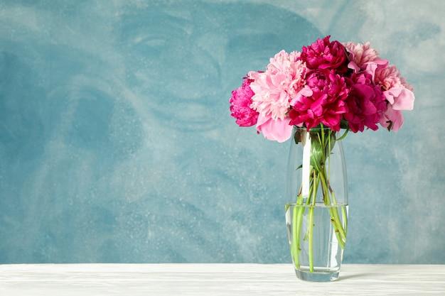 Vaso de vidro com buquê de peônias lindas na mesa branca contra um fundo azul