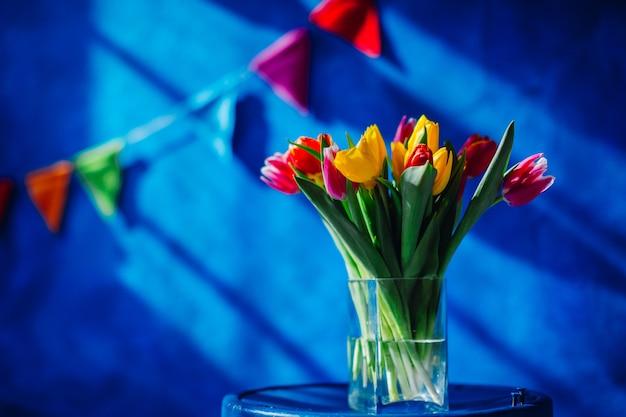 Vaso de vidro com buquê de tulipas vermelhas, amarelas e cor de rosa