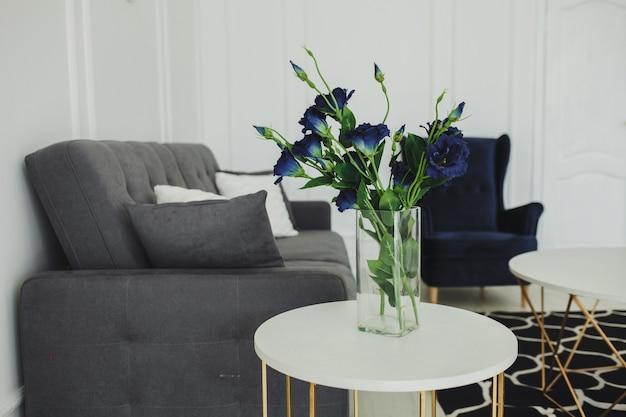 Vaso de vidro com flores em um interior moderno com sofá e carpete