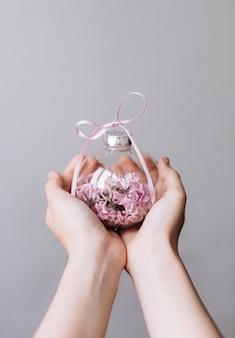 Vaso de vidro com flores lilás mãos centro